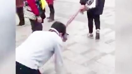 男子被女子用围巾牵引 跪地爬行学狗叫